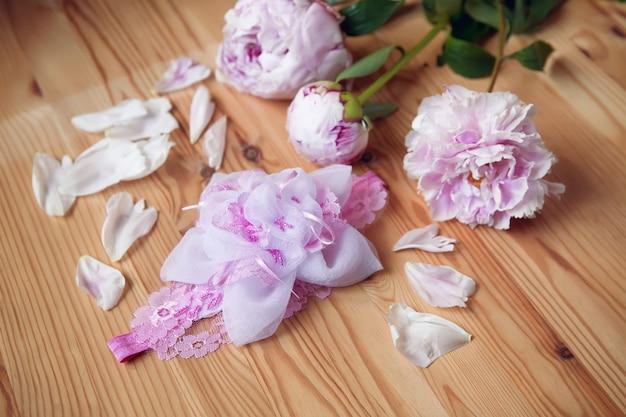 Fascia per capelli, fiore in tessuto e pizzo, perline con peonia su superficie in legno