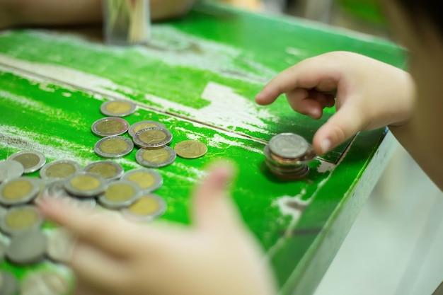 Bambino che tiene in mano una moneta per lo stack e salva il suo budget per il futuro.