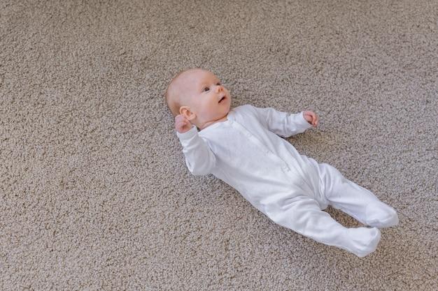 Concetto di bambino, neonato e infanzia - vista dall'alto del bambino sul pavimento