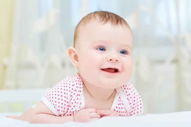 Bambino, neonato sorridente mentre giaceva su un letto bianco.