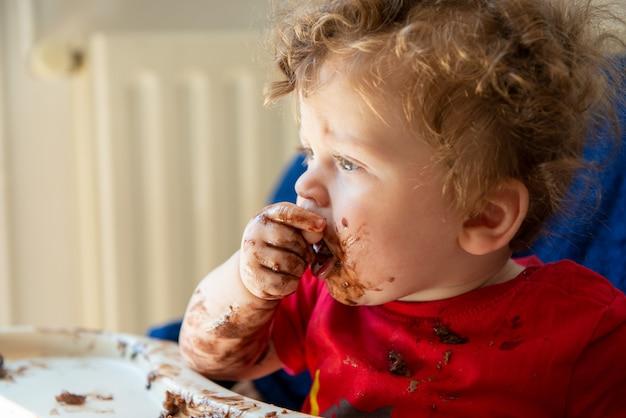Il bambino sta mangiando una torta al cioccolato