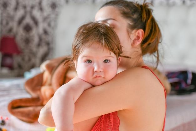 Il bambino è felice tra le braccia della mamma. mamma sorridente. spendere gioiosamente insieme. arredamento. quando papà è al lavoro