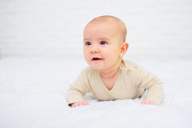 Il bambino è sdraiato a pancia in giù e sorride su bianco