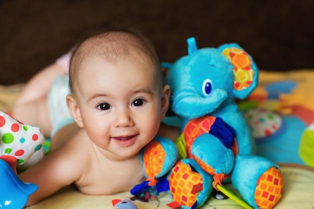 Il bambino è sdraiato sulla pancia e abbraccia un elefante giocattolo.