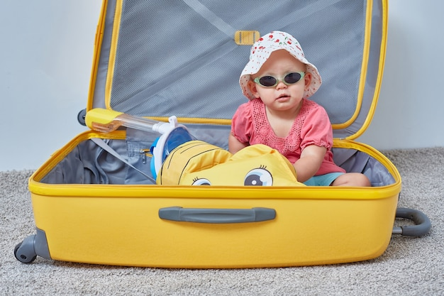 Il bambino è seduto in una valigia con cose estive per le vacanze