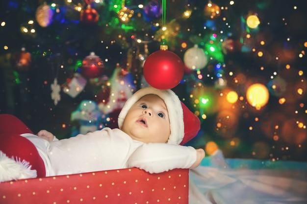 Il bambino è sotto l'albero, natale. messa a fuoco selettiva. vacanza.