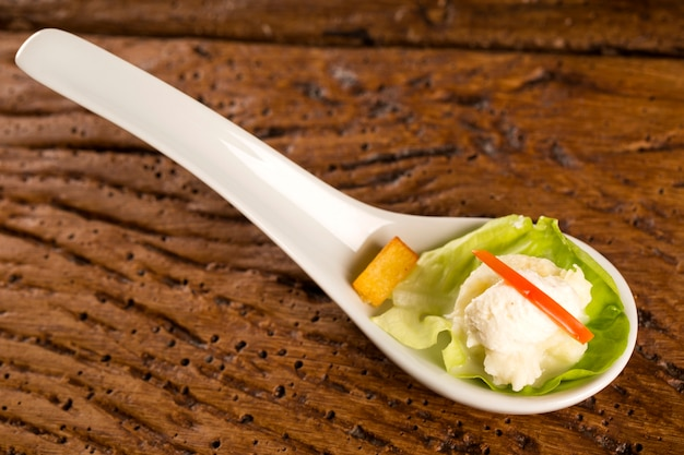 Insalata di lattuga, pomodorini, cuori di palma, salsa di cavolfiore, manioca fritta e panna montata salata in un cucchiaio. assaggia il fingerfood della gastronomia