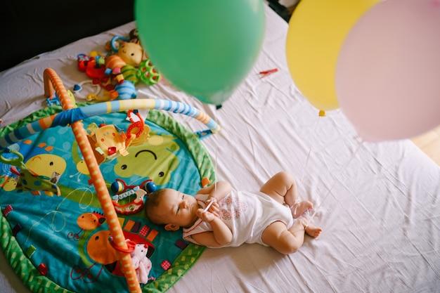 Il bambino giace sul letto accanto a giocattoli e palloncini