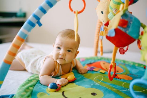 Il bambino giace a pancia in giù su un tappetino da gioco e tiene in mano un sonaglio