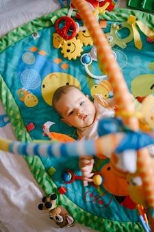 Il bambino si sdraia su un tappetino da gioco e raggiunge i giocattoli appesi sopra di lui
