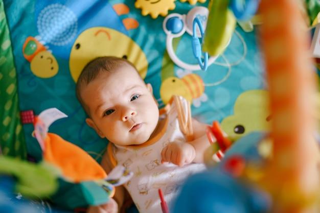 Il bambino giace su un tappetino da gioco con dei giocattoli appesi sopra di lui