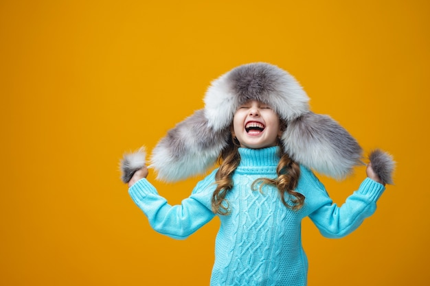 Bambina in un cappello di pelliccia bianca