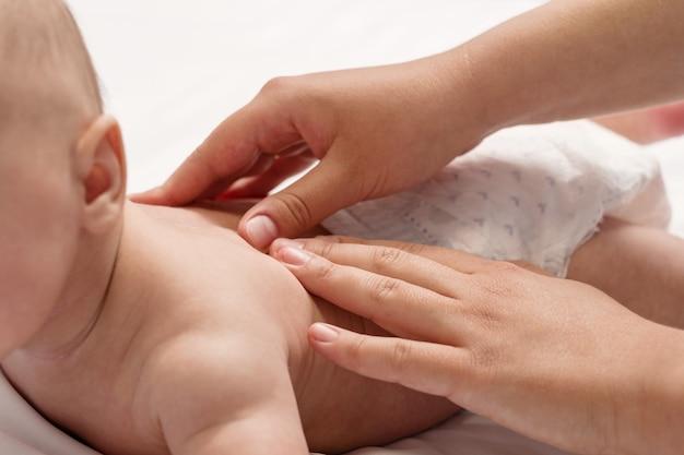 Massaggio del bambino, mani del primo piano sulla schiena del bambino