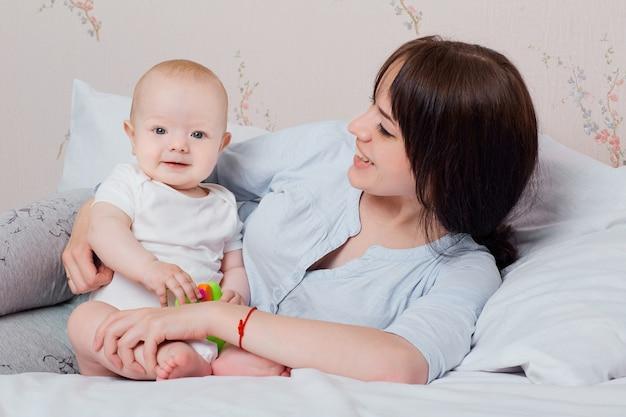 Il bambino e la mamma in pigiama giocano di buon umore sul letto ridendo e divertendosi in un'atmosfera familiare e accogliente