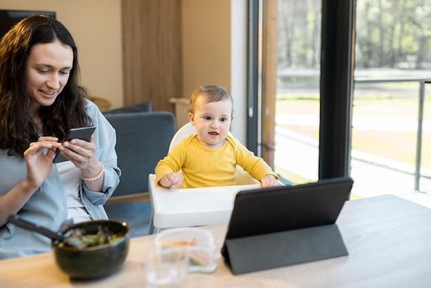 Bambino e genitori impegnati in un gadget digitale durante un pranzo a casa