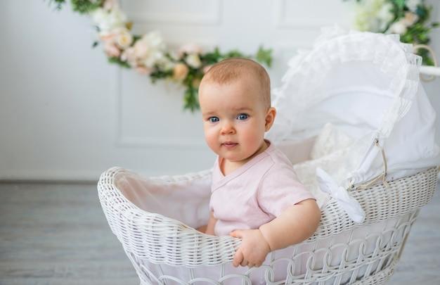 Il bambino in un body rosa si siede in un passeggino retrò su uno sfondo bianco con fiori