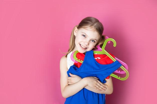 Bambino su un muro rosa, la bambina tiene due abiti di diversi colori, si rallegra di comprarne due al prezzo di uno