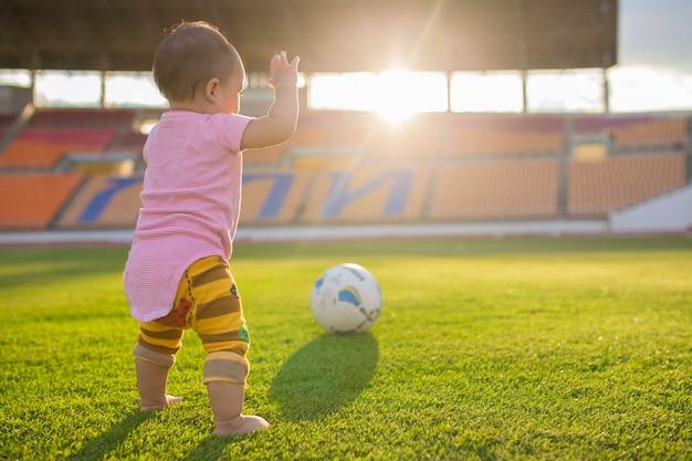 Bambino che gioca footbal o soccerl nello stadio con il tramonto