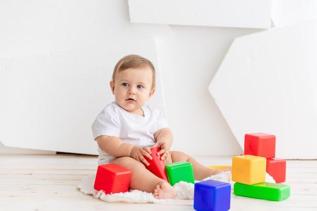 Bambino che gioca con i cubi colorati in una stanza luminosa di casa