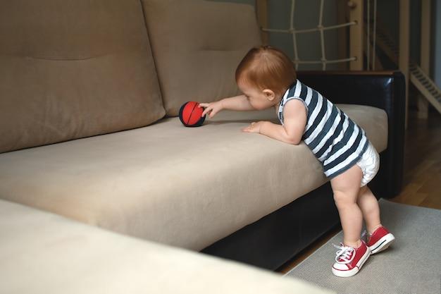 Il bambino fa sport a casa, il culo del bambino in un pannolino.