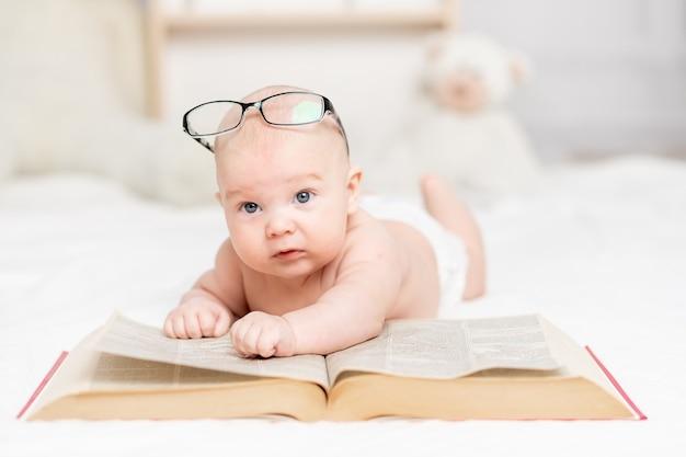 Bambino che legge un libro o lo guarda nel concetto di scuola materna, apprendimento e sviluppo