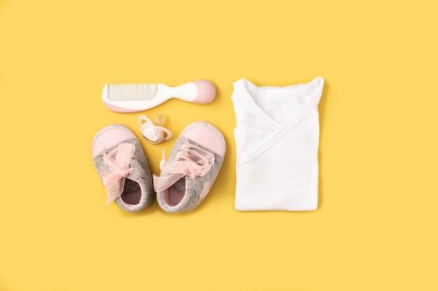 Pagliaccetto, scarpe, ciuccio e pettine per capelli sulla superficie gialla