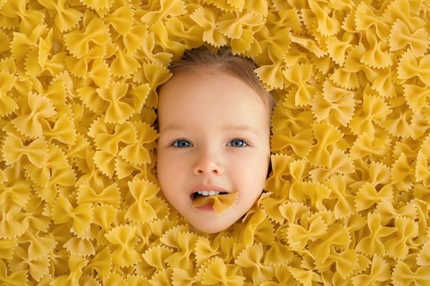 Il viso del bambino è circondato da una grande quantità di maccheroni.