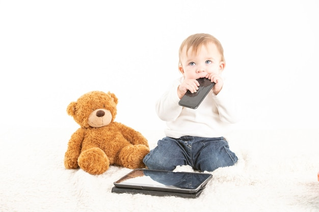 Viso del bambino con un cellulare in bocca accanto a un orsacchiotto e un tablet.