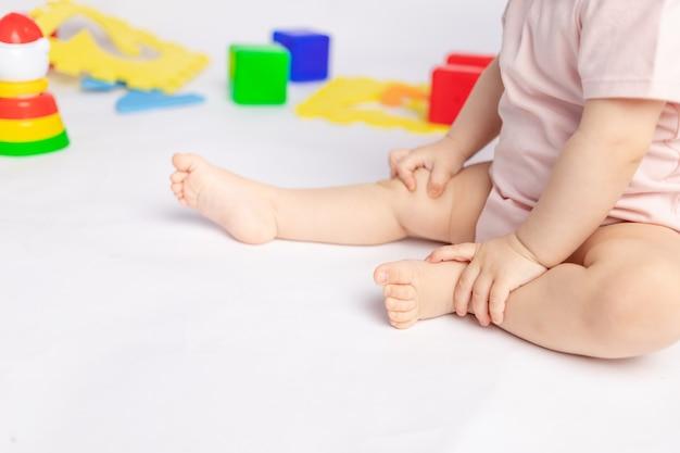 I piedi del bambino su uno sfondo bianco isolato tra i giocattoli, spazio per il testo