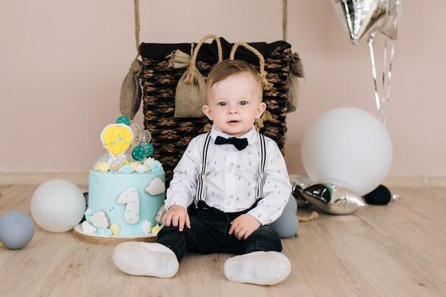 Primo compleanno del bambino il bambino sorridente sveglio è festa per bambini di 1 anno con palloncini