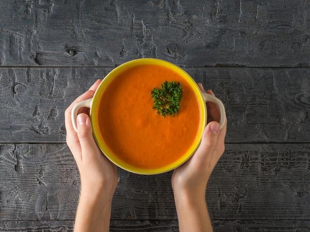 Le mani del bambino tengono una pentola di zuppa di panna fresca su un tavolo di legno. zuppa della dieta vegetariana. lay piatto. la vista dall'alto.