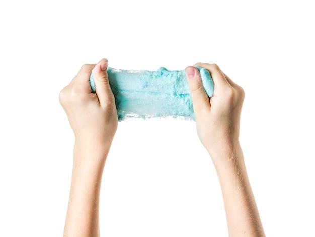 Le mani del bambino allungano la calce turchese isolata su sfondo bianco. giocattolo antistress. giocattolo per lo sviluppo delle capacità motorie manuali.