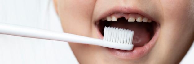 Bocca del bambino con un buco per il dente da latte e uno spazzolino da denti. lavarsi i denti, contare i denti.