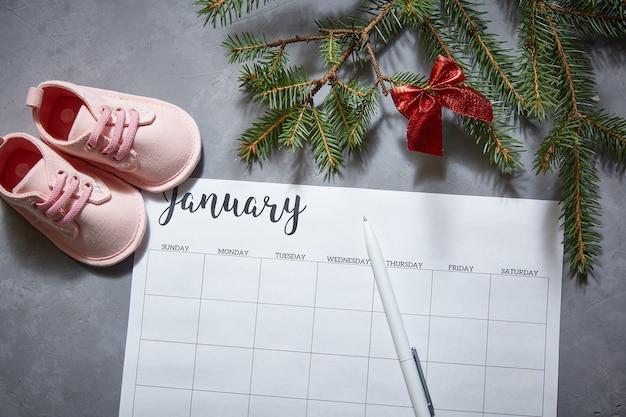 Scarpe per bambini, calendario invernale per gennaio. l'annuncio della gravidanza.