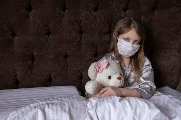 Ragazza triste del bambino nella mascherina medica che si trova con l'orsacchiotto a letto