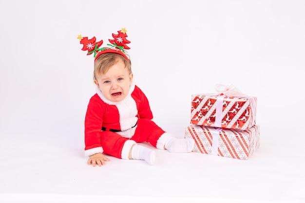 Bambino in costume da babbo natale con doni