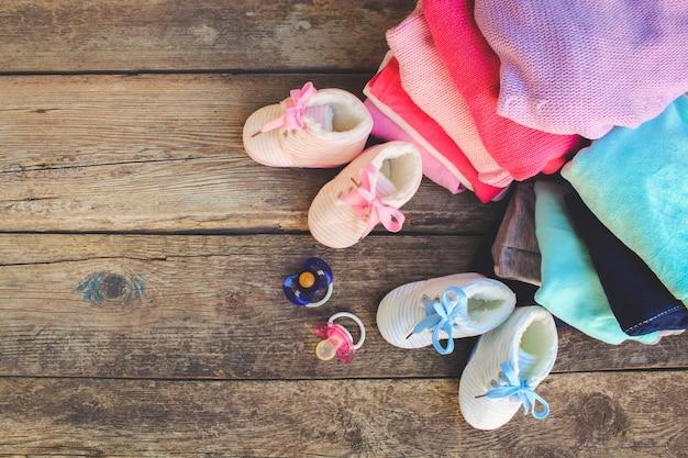 Scarpe per bambini, vestiti e ciucci rosa e blu sul legno vecchio