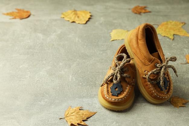 Scarpe e foglie di bambino su fondo strutturato grigio.