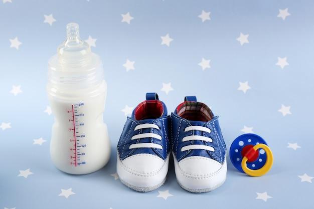 Scarpe per bambini con capezzolo e bottiglia di latte su sfondo blu