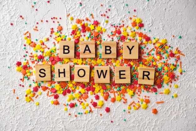 Parole di legno della doccia di bambino sui coriandoli variopinti, su fondo strutturato bianco