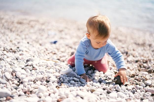 Il bambino si siede in ginocchio su una spiaggia di ciottoli con una pigna tra le mani e la guarda