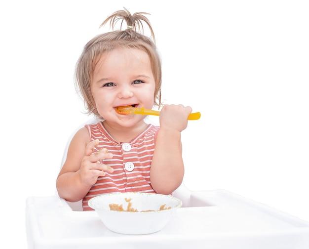 Baby sitter in sedia e mangiare porridge con cucchiaio isolato su sfondo bianco