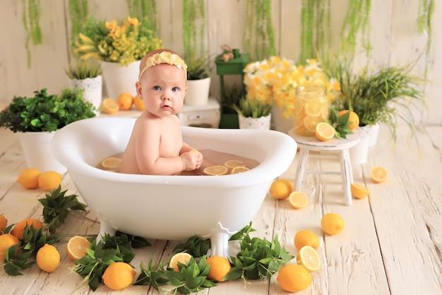 Baby sitter nella piccola vasca da bagno facendo un bagno con fette di limoni in acqua