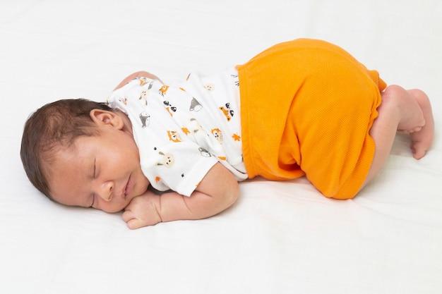 Bambino che dorme nel letto vista dall'alto di tutto il corpo. e pantaloni arancioni.