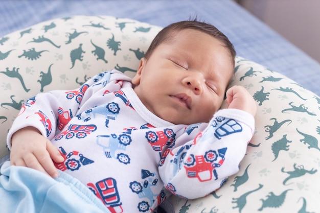 Bambino che dorme con il braccio sulla pancia e con vista dall'alto