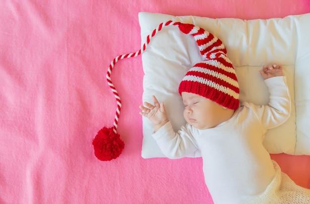 Il bambino dorme in un cappello da babbo natale, concetto di natale