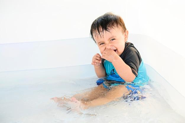 Bambino che sorride e che gode dell'acqua in una piscina