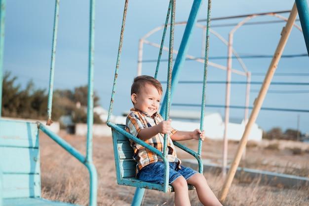 Bambino sull'altalena che dondola vicino al mare, in camicia e pantaloncini di jeans