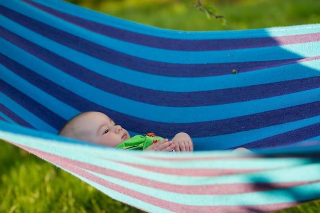 Un bambino dondola su un'amaca in giardino in una giornata di sole.