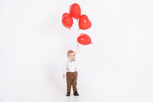 Neonato del bambino in vestito che tiene palloncino cuore sul muro bianco. il giorno di san valentino e il concetto di amore